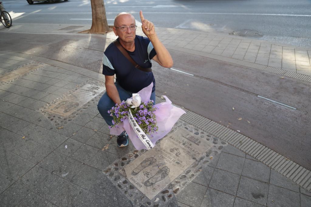 Un hombre deja un ramo de flores en homenaje a Luis Salom