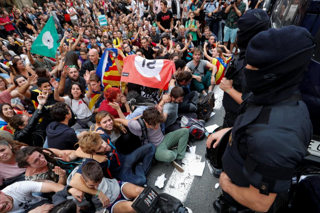 People shout slogans during a protest as Catalan regional police officers stand guard outside National Police station, in Barcel