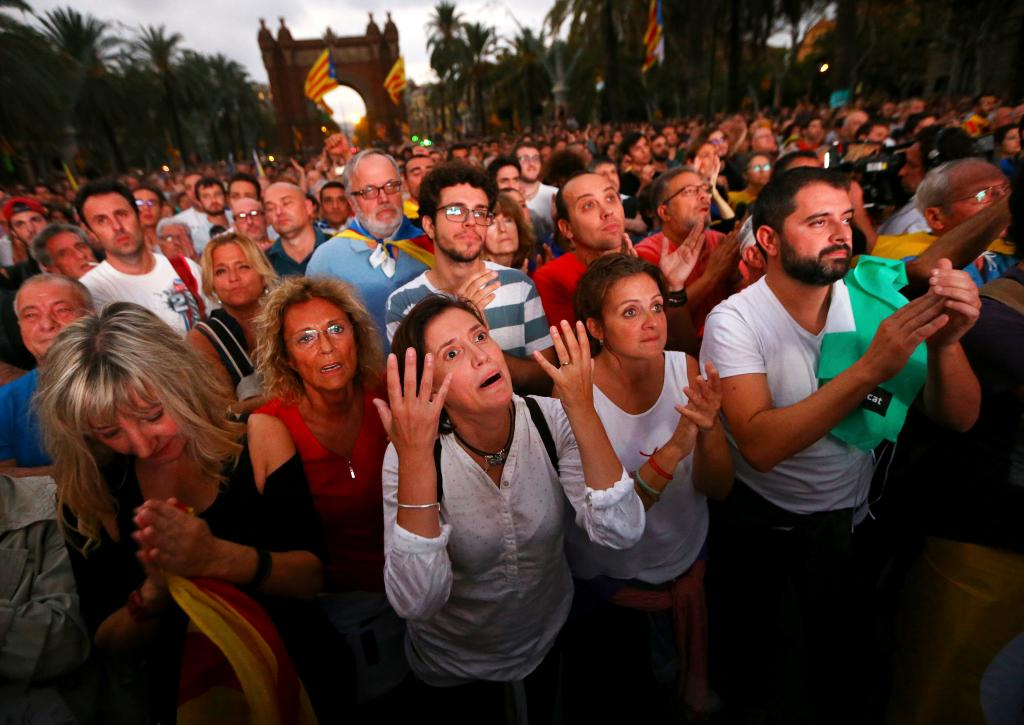 People react as they watch a sesion of the Catalonian regional parliament on a giant screen at a pro-independence rally in Barce