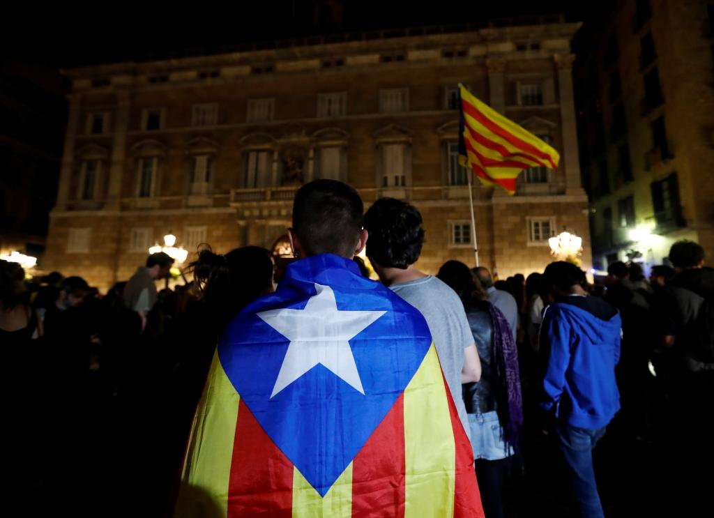 A man wears an Estelada, Catalan separatist flag, as protesters gathered outside the regional government headquarters after Spai