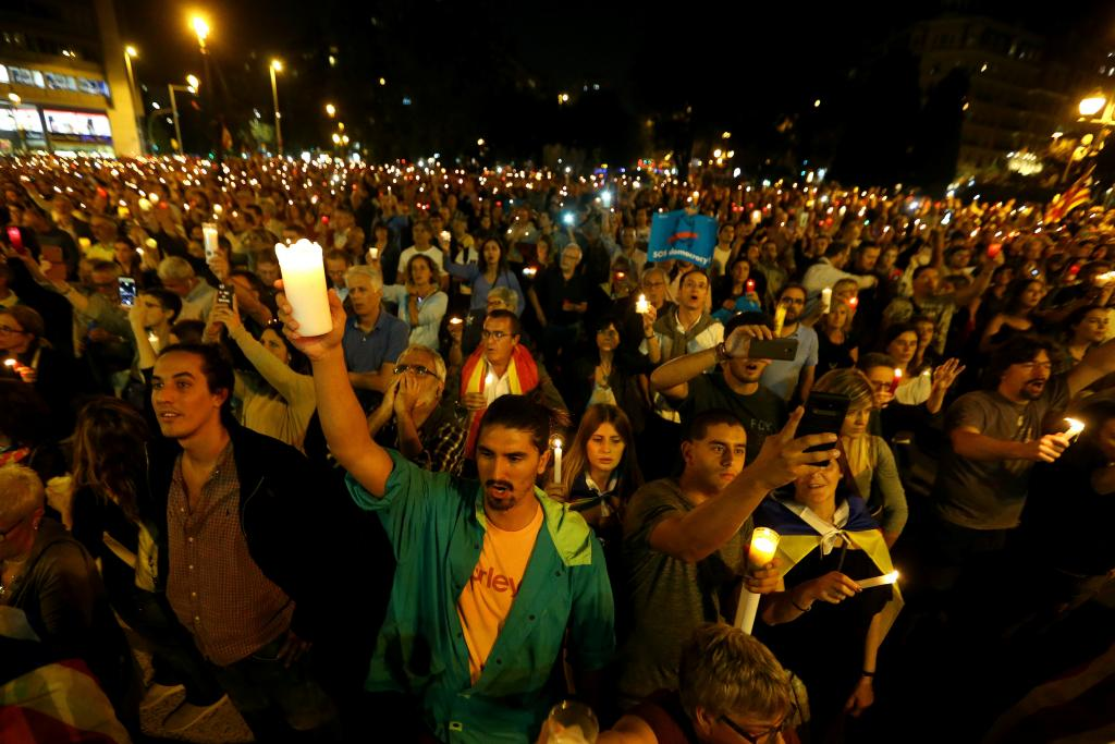 People hold candles during a gathering to protest against the imprisonment of leaders of two of the largest Catalan separatist o