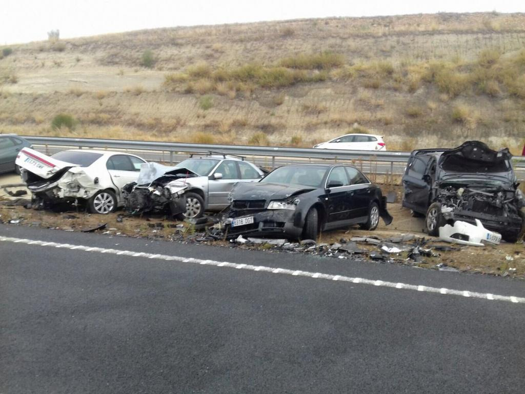 Wrecked cars are seen at the scene of an accident involving multiple vehicles, caused by heavy fog on a road near Galisteo
