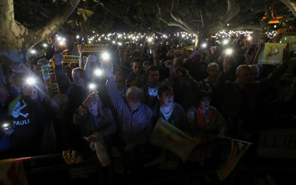 People hold their mobile phones during a gathering in support of the members of the dismissed Catalan cabinet after a Spanish ju