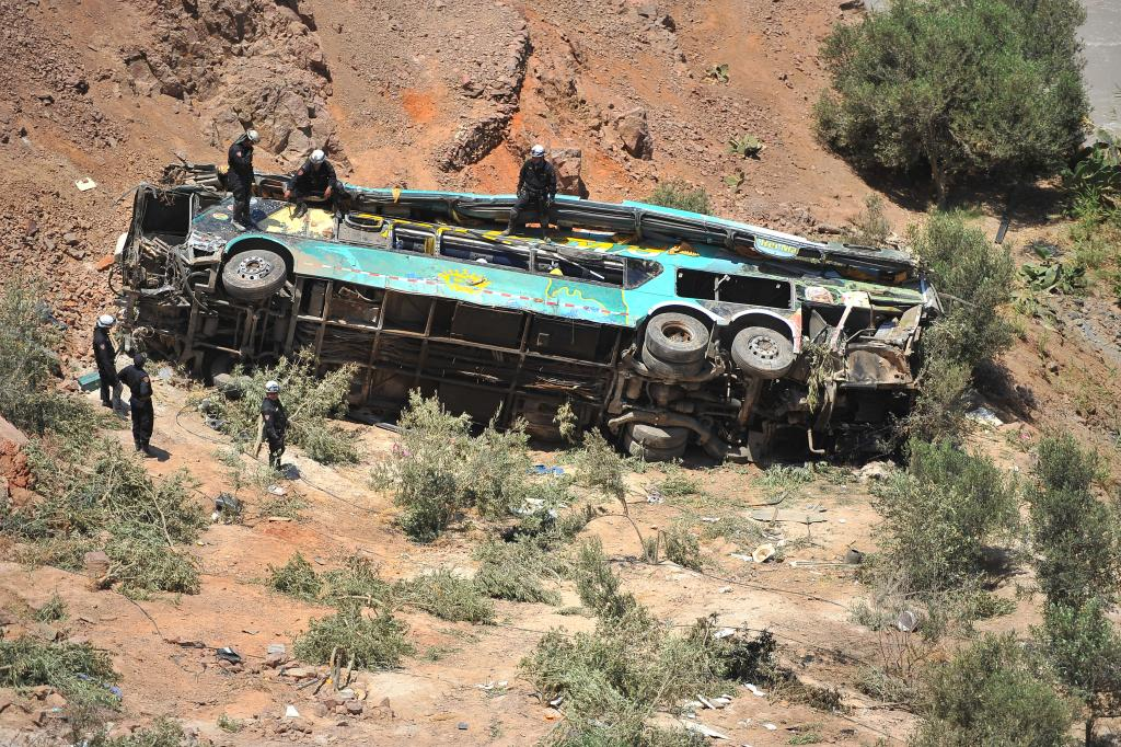 Rescue workers attend to the scene after a bus falls into a ravine in Arequipa