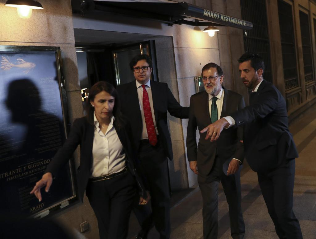 Spain's Prime Minister Mariano Rajoy is led to his car as he leaves a restaurant following a motion of no confidence debate at P