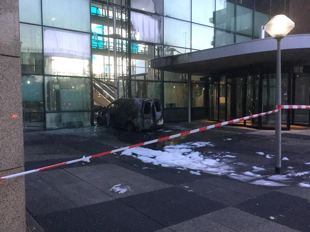 A van is seen burned out after crashing into the glass facade of the head office of Dutch newspaper De Telegraaf in what police