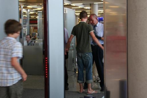 Un miembro de la seguridad privada del aeropuerto de Son Sant Joan inspecciona a un viajero en un punto de control.