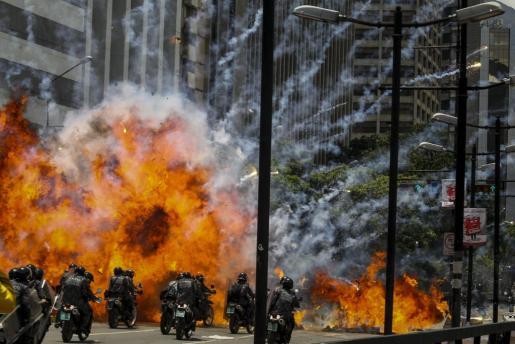 Fotografía de una explosión en medio de varios policías motorizados en inmediaciones de la Plaza Altamira de Caracas.