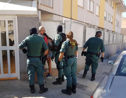 Agentes de la Guardia Civil con una de las detenidas de la calle Murtà.