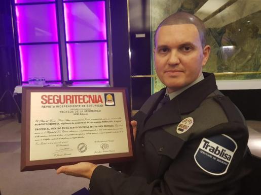 El vigilante posa con el diploma que le acredita como merecedor del trofeo al mérito a la seguridad privada 2017.