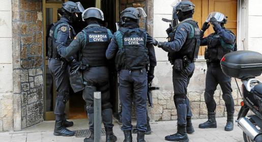 Agentes de la Guardia Civil, entrando en una de las casas.