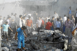 Men search for bodies under rubble of a house, destroyed by a Syrian Air force air strike, in a village of Tel Rafat