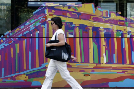 A woman walks past an advertisement on a bus depicting the Parthenon in Athens