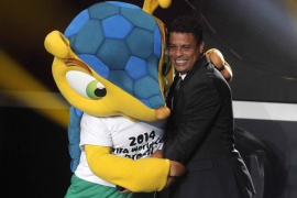 Former Brazilian soccer player Ronaldo is hugged by mascot of 2014 FIFA soccer world championships during FIFA Ballon d'Or 2012