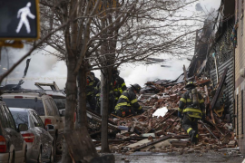 Firefighters search through debris and rubble at the site of a building collapse and fire in Harlem