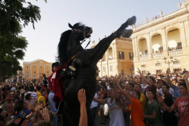 A rider rears up on his horse while surrounded by a cheering crowd during the traditional Fiesta of San Joan in downtown Ciutade