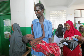 An internally displaced man carries his son who is suffering from cholera into the paediatric ward at the Banadir hospital in So