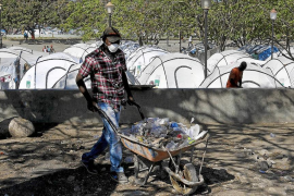 Workers clean up a camp which housed people displaced by an earthquake for almost two years, in Port-au-Prince