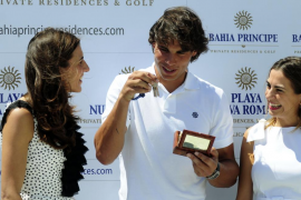 Spanish tennis player Nadal stands with sisters Isabel and Lidia Pinero as he holds up keys to his new beach home located in Res