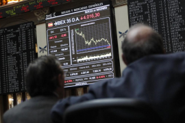 Traders look at screens at the Madrid bourse